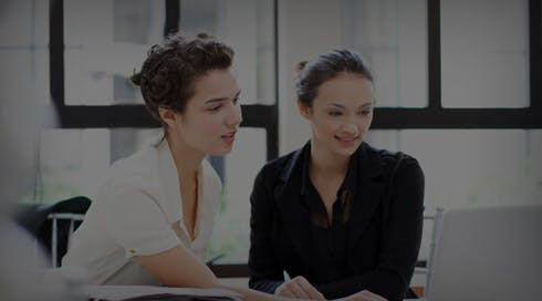 two women in advertising smiling and looking at a computer