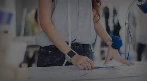 girl wearing blue sleeveless blouse measuring a fashion drawing
